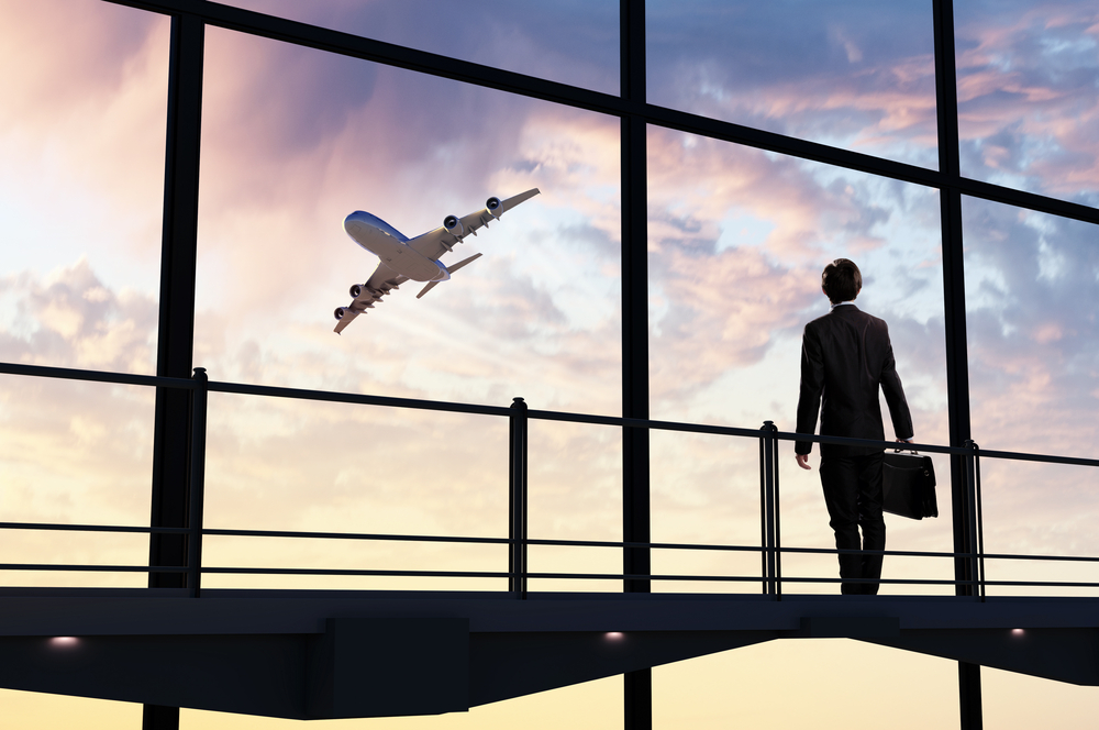 Image of businessman at airport looking at airplane taking off-1